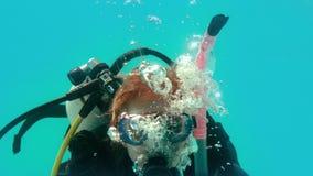 Kobieta patrzeje kamerę podwodną w akwalung przekładni zbiory