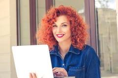 Kobieta patrzeje kamerę używać laptop obrazy royalty free