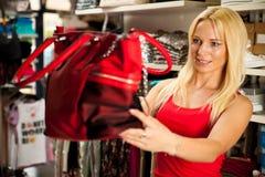 Kobieta patrzeje kiesy torbę w sklepie - zakupy Zdjęcia Royalty Free