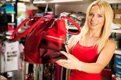 Kobieta patrzeje kiesy torbę w sklepie - zakupy Zdjęcie Royalty Free