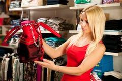 Kobieta patrzeje kiesy torbę w sklepie - zakupy Obrazy Royalty Free