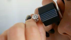 Kobieta patrzeje kolczyka z diamentami przez jubilera loupe Jubiler ocenia wartość luksusowi kolczyki zdjęcie wideo