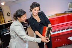 Kobieta patrzeje kolor opcje dla pianina Zdjęcia Stock
