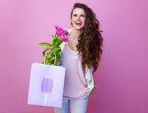 Kobieta patrzeje kopię z bukietem tulipany i torba na zakupy Fotografia Stock