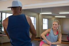 Kobieta patrzeje męskiego tancerza w studiu Obrazy Stock