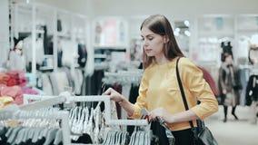 Kobieta patrzeje odziewa na poręczu w sklepie odzieżowym Stylowy i moda pojęcie Młoda dama wybiera bluzkę, odziewa zbiory wideo