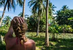 Kobieta patrzeje pięknego tropikalnego widok z drzewkami palmowymi i małym stawem Obraz Stock