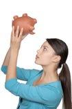 Kobieta patrzeje prosiątko banka widzieć jeżeli jakaś pieniądze opuszczać obrazy stock