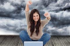Kobieta patrzeje prosto naprzód gdy świętuje przed jej laptopem Zdjęcia Stock
