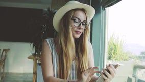 Kobieta patrzeje przez obrazków na smartphone w kawiarni Młodej dziewczyny pić kawowy i uśmiechnięty zbiory