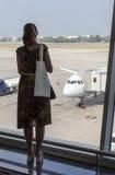 Kobieta patrzeje przez okno przy samolotami w lotnisku obraz stock