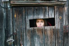 Kobieta patrzeje przez pęknięcia zamknięta drewniana jata Fotografia Royalty Free