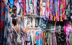 Kobieta patrzeje różne kolorowe koszula podczas gdy odzieżowy shopp zdjęcia stock