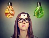 Kobieta patrzeje szybkie żarcie i zieleni warzyw żarówkę Obraz Royalty Free