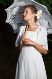 Kobieta patrzeje upwards w białej sukni i z koronkowym parasolem Zdjęcia Royalty Free