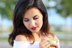 Kobieta patrzeje w dół trzymający filiżankę outdoors fotografia royalty free