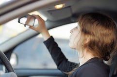 Kobieta patrzeje w lustrze w samochodzie Obrazy Royalty Free