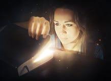 Kobieta patrzeje w rozjarzoną biblię. Zdjęcie Stock