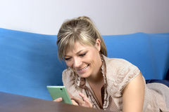 Kobieta patrzeje w telefon na kanapie indoors Zdjęcie Royalty Free