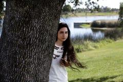 Kobieta Patrzeje Wokoło Dębowego Drzewnego bagażnika W parku zdjęcie royalty free