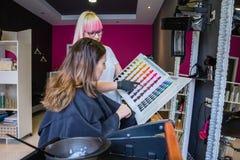Kobieta patrzeje z fryzjerem włosianego barwidła paletę zdjęcie stock