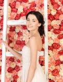 Kobieta pełno z starą drabiną i tło róże Obraz Stock