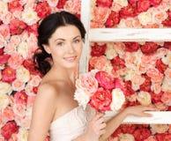 Kobieta pełno z starą drabiną i tło róże Fotografia Stock