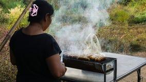 Kobieta piec na grillu kiełbasy przy pospolitym plenerowym parkiem Obraz Stock
