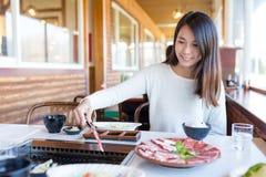 Kobieta piec pokrojonego wołowina w japońskim yakiniku obraz stock
