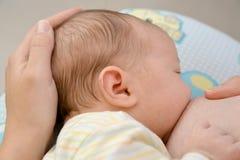 Kobieta pielęgnuje dziecka piersią Zdjęcia Stock
