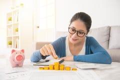 Kobieta pieniądze odliczający wierza od savings obraz stock