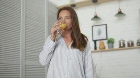 Kobieta pije świeżego sok pomarańczowego w ranku w kuchni zbiory wideo