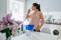 Kobieta pije filtrującą wodę od filtrowego dzbanka w kuchni nowoczesna kuchnia projektu Zdrowy Styl życia Zdjęcia Royalty Free