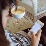 Kobieta pije gorącą kawę w kawiarni i używa telefon komórkowego obraz royalty free