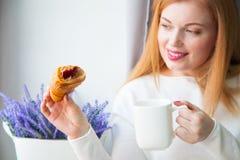 Kobieta pije herbaty i croissants z dżemem Zamarznięta babeczka zdjęcie royalty free
