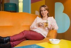 Kobieta pije herbaty z ciastkami Zdjęcie Royalty Free