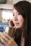 Kobieta pije i opowiada na telefonie komórkowym. Zdjęcie Royalty Free