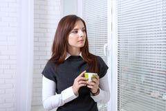 Kobieta pije kawę blisko okno obraz stock