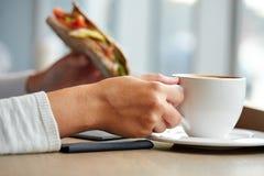 Kobieta pije kawę i je kanapkę przy kawiarnią Obrazy Stock