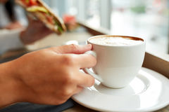 Kobieta pije kawę i je kanapkę przy kawiarnią Zdjęcia Stock