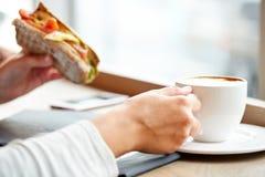 Kobieta pije kawę i je kanapkę przy kawiarnią Zdjęcie Stock