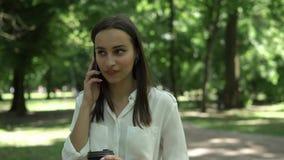 Kobieta pije kawę i opowiada na jej telefonie w parku zbiory wideo