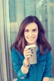 Kobieta pije kawę outdoors trzyma papierową filiżankę obraz stock