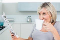 Kobieta pije kawę podczas gdy czytający gazetę Fotografia Royalty Free