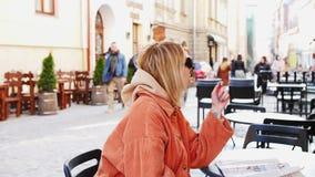 Kobieta pije kawę w kawiarni Ruchliwie miasto ruch drogowy Za okno ZWOLNIONE TEMPO 4K DCi Dziewczyna cieszy się gorącego napój da zbiory