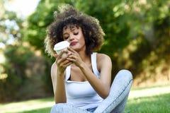 Kobieta pije kawę w parku z afro fryzurą Zdjęcia Stock