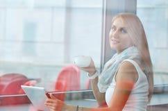 Kobieta pije kawę w ranku przy restauracją Zdjęcie Royalty Free