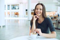 Kobieta pije kawę w ranku przy restauracyjną miękką ostrością obrazy stock