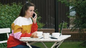 Kobieta pije kawowego i opowiadać na telefonie komórkowym zbiory wideo