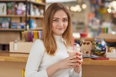 Kobieta pije koktajl przy barem Ładna dziewczyna z blondynem, w białej przypadkowej koszula z czerwonym modnym manicure'em Potoms obrazy royalty free